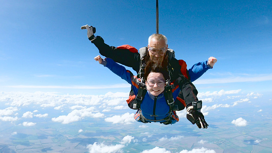 A woman is enjoying her first parachute jump. She jumped with an experienced skydiving instructor.