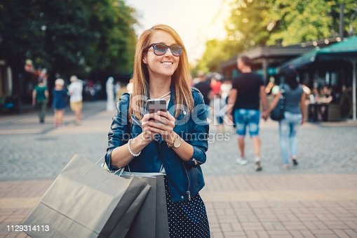 Young woman in the city holding shopping bags and texting