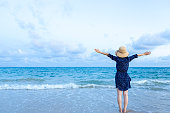 istock Happy woman enjoying freedom with open hands on sea 1154925453