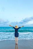 istock Happy woman enjoying freedom with open hands on sea 1154925466
