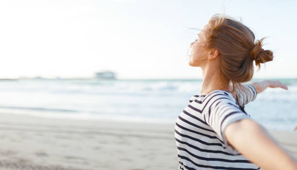 happy woman enjoying freedom with open hands on sea stock photo