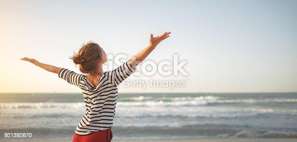 istock happy woman enjoying freedom with open hands on sea 921392670