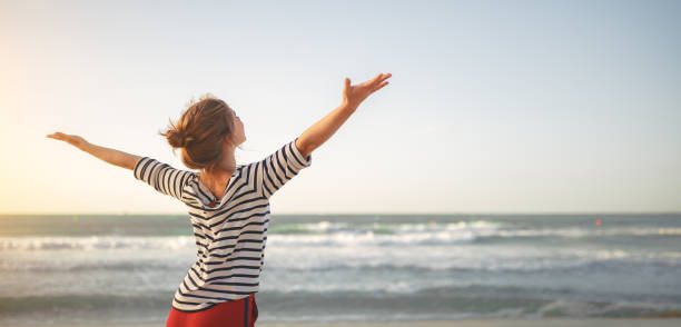 happy woman enjoying freedom with open hands on sea happy young woman enjoying freedom with open hands on sea freedom stock pictures, royalty-free photos & images