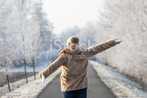 Fashion model wearing fur coat and knitted hat with arms outstretched outdoors. Cold weather with frozen trees