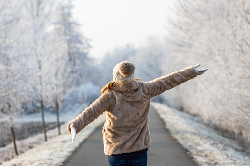 Happy woman enjoying fresh air during walk in winter nature
