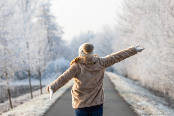 Happy woman enjoying fresh air during walk in winter nature stock photo