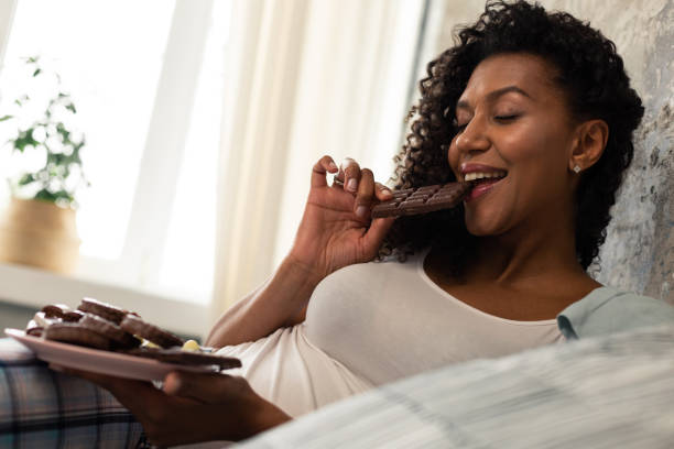 Happy woman enjoying her chocolate bar in bed. stock photo