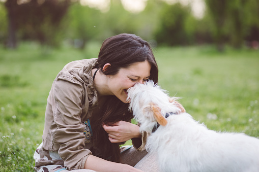 Happy woman enjoying her dog in the park
