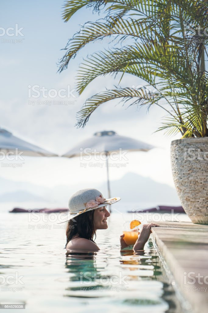 Happy woman enjoying in summer day at swimming pool. royalty-free stock photo