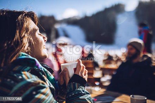 Young happy woman enjoying while drinking tea and sunbathing at ski resort.