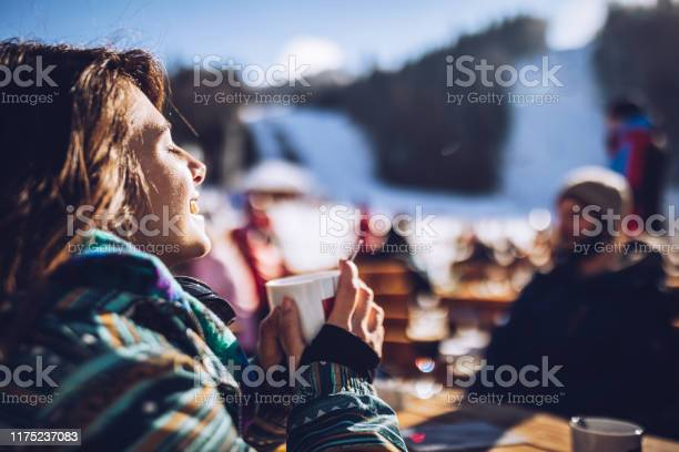 Photo of Happy woman enjoying in sun and tea at ski resort.