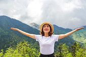 istock Happy Woman Enjoying Nature on meadow on top of mountain 1142138007