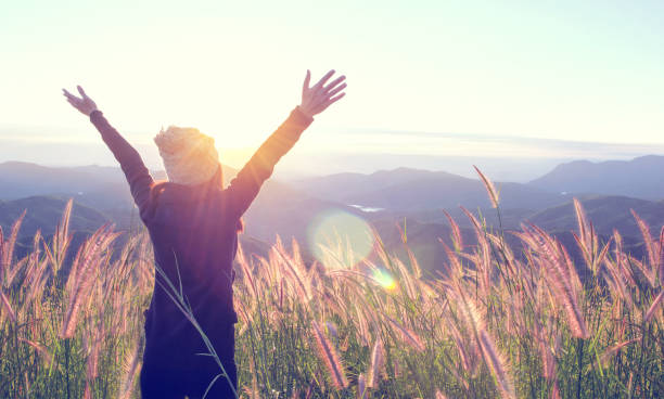 Happy Woman Enjoying Nature on meadow on top of mountain with sunrise. Outdoor. Freedom concept. stock photo