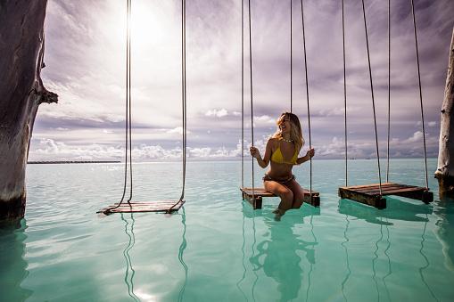 Happy woman enjoying on a swing in the sea.