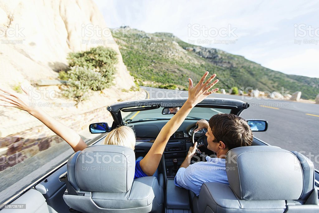 Happy Woman Enjoying Road Trip While Man Driving Convertible royalty-free stock photo