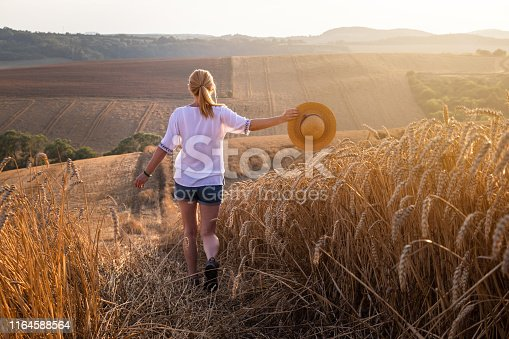 1094815168 istock photo Happy woman enjoying summer at countryside during sunset. 1164588564