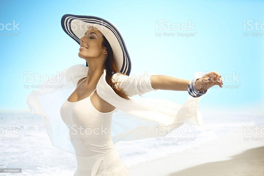 Happy woman enjoying summer sun on beach stock photo