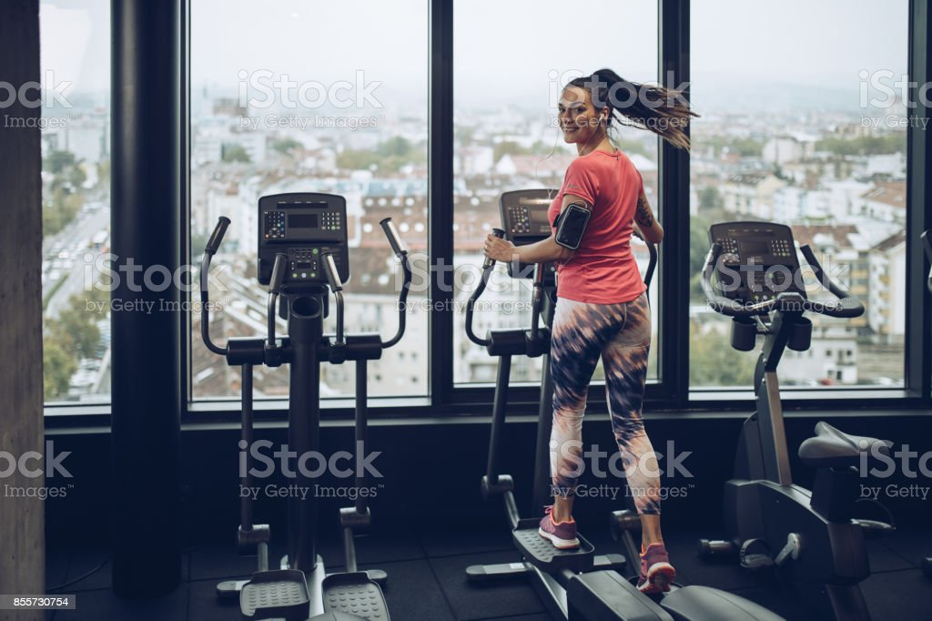 Happy woman exercising on a cross trainer in a gym. stock photo