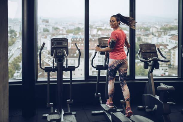 happy woman exercising on a cross trainer in a gym. - ellipse stock photos and pictures