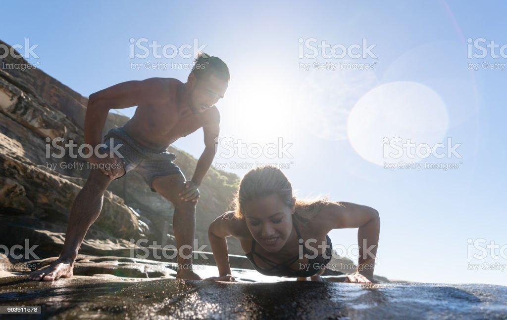 Happy woman exercising outdoors with her personal trainer - Royalty-free Adult Stock Photo