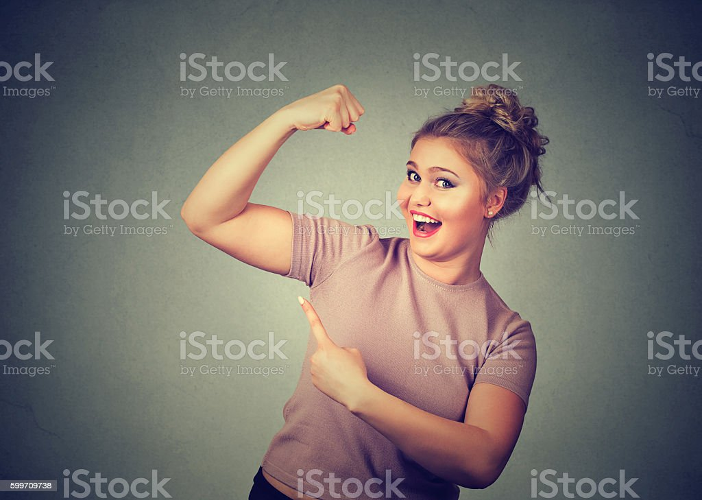 happy woman flexing muscles showing her strength stock photo