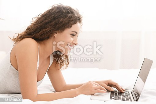 660640646 istock photo Happy woman flirting online on laptop in bed 1134246609