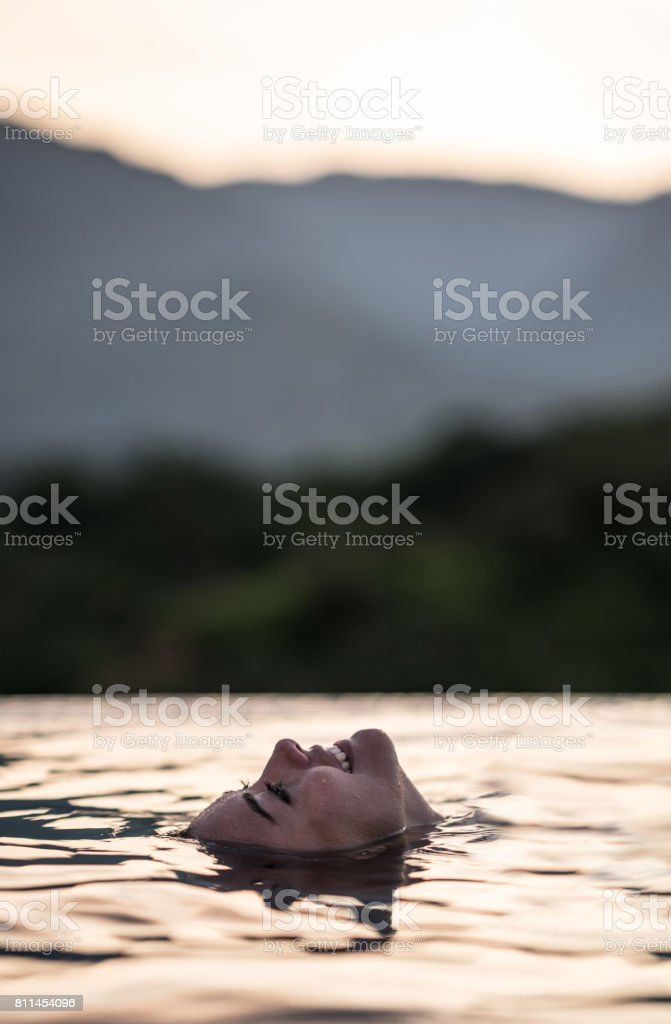 Happy woman floating in the swimming pool stock photo