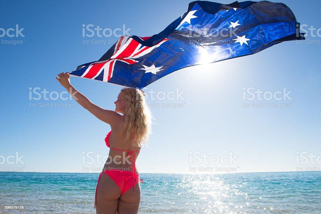 Happy woman flying Australian flag at beach stock photo