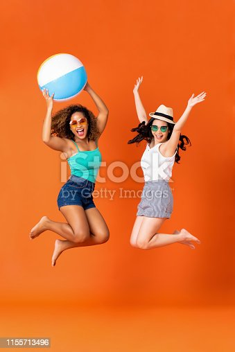 istock Happy woman friends in casual summer clothes jumping 1155713496