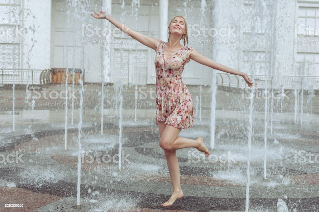 Happy woman frolics in a fountain. stock photo