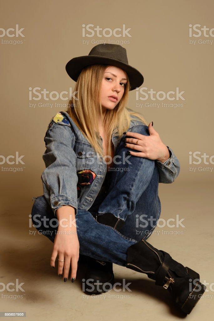 5d3f76ea745e Retrato de cuerpo entero de mujer feliz. chica sentada en un piso estilo  adolescente.