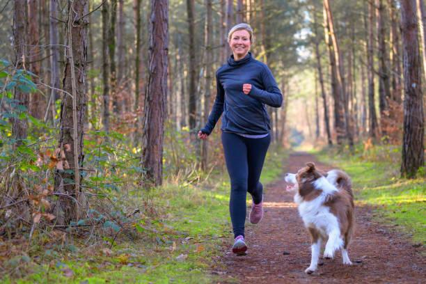 Happy woman full of vitality exercising her dog stock photo