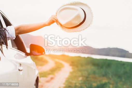 Happy woman hand holding hat outside open window car with meadow and mountain lake background. People lifestyle relaxing as traveler on road trip in holiday vacation. Transportation and travel concept