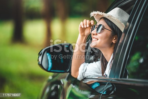 istock Happy woman hand holding hat outside open window car with meadow and mountain lake background. People lifestyle relaxing as traveler on road trip in holiday vacation. Transportation and travel concept 1175716007
