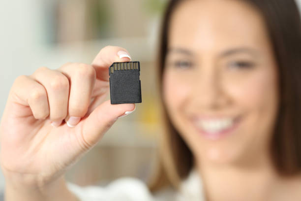 happy woman hand showing a memory card - memory card stock photos and pictures