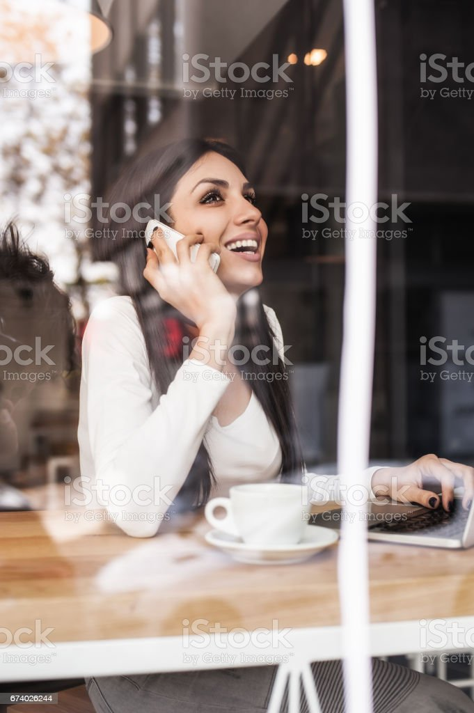 Happy woman having cell telephone conversation while sitting in cafe royalty-free stock photo