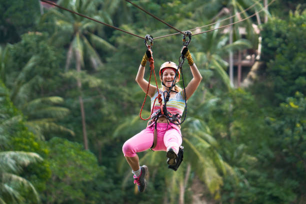 Happy woman having fun during canopy tour in the forest. Young cheerful woman rappelling from a zip line during canopy tour in nature. zip line stock pictures, royalty-free photos & images