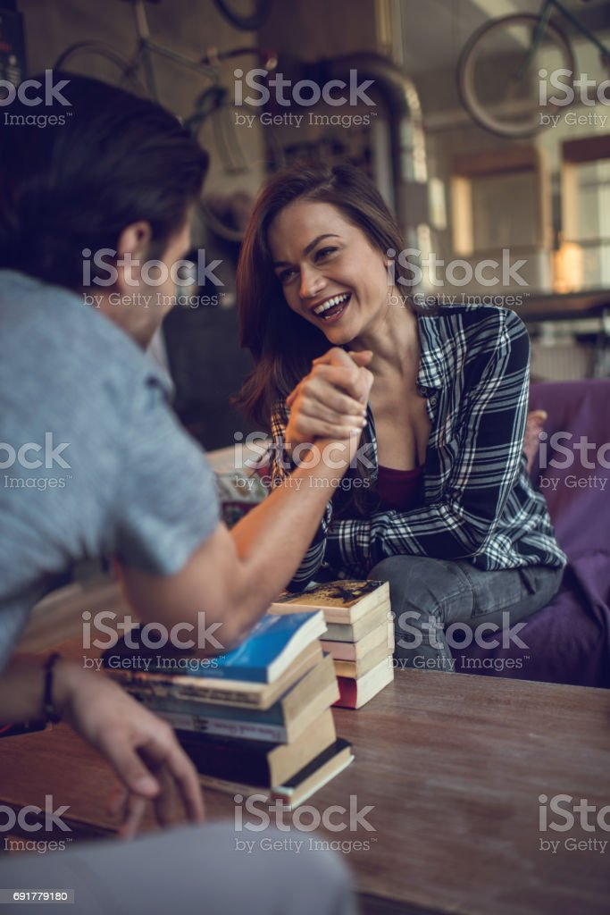 Happy woman having fun while arm wrestling with her boyfriend. stock photo