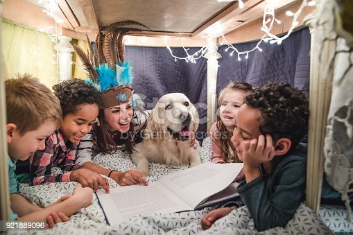 istock Happy woman having fun while reading stories to group of kids in a tent. 921889096