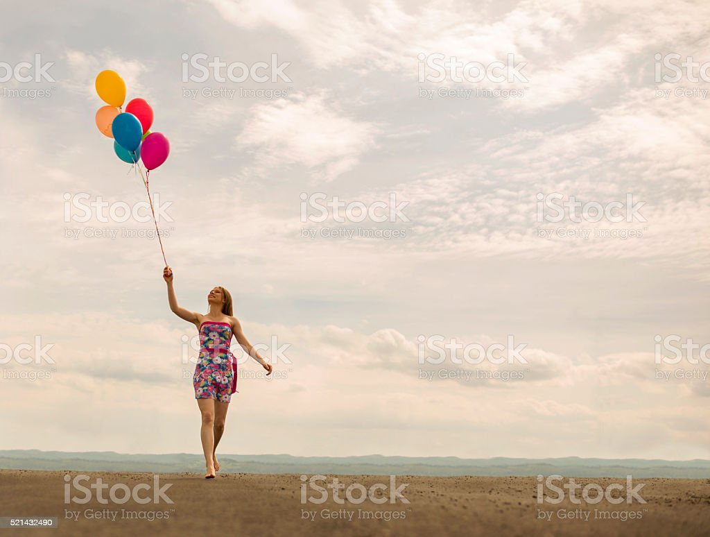 Happy woman having fun with group of multi colored balloons stock image