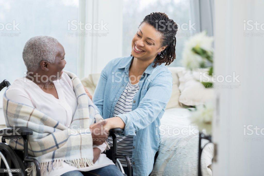 Happy woman helps elderly mother stock photo