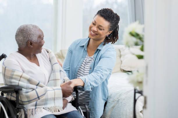 glückliche frau hilft älteren mutter - altenpfleger stock-fotos und bilder