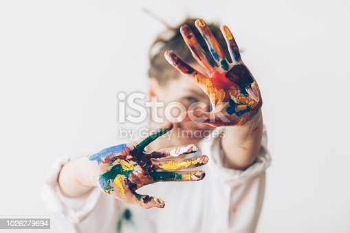 Happy woman hiding the face with her painted hands. Creative, art, childhood, drawing concept