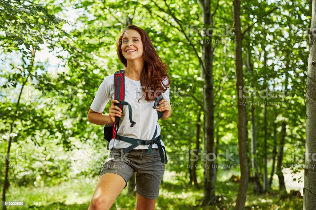 Happy woman hiking in the woods stock photo