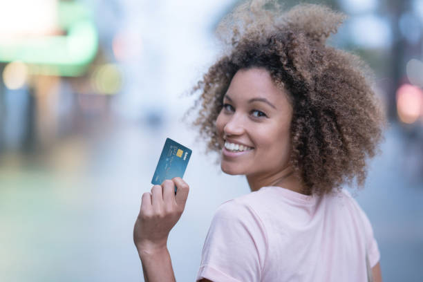 Happy woman holding a credit card and smiling stock photo
