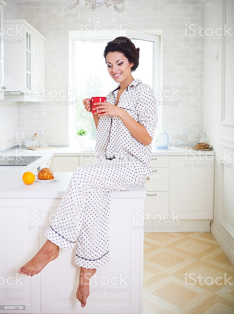 Happy woman holding a cup of coffee wearing pajamas stock photo