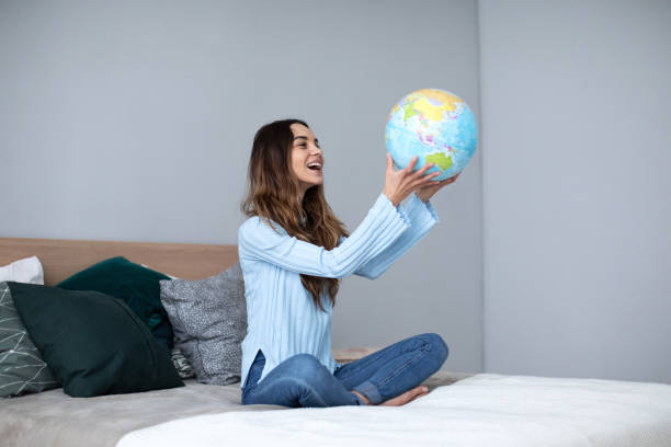 Happy woman holding a globe, indoor. stock photo