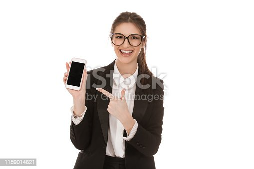 1132512623istockphoto Happy woman holding a smart phone pointing with other hand to it 1159014621