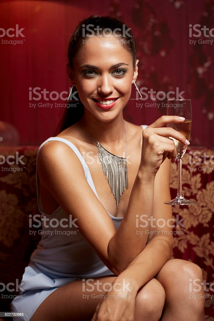 Happy woman holding champagne flute at nightclub stock photo