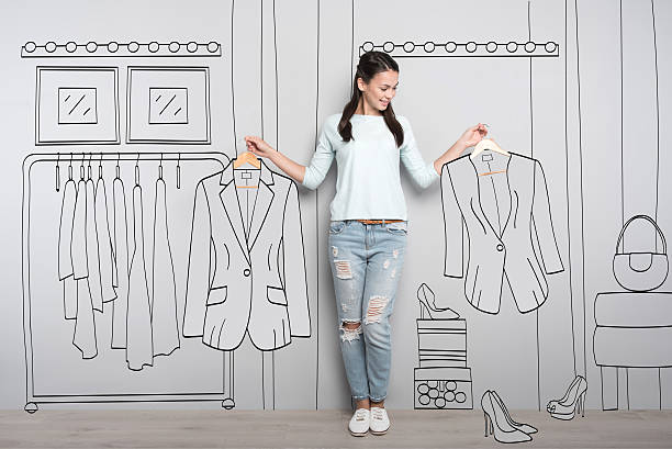 happy woman holding clothes on hangers - garment stock photos and pictures